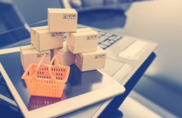 Orange shopping cart and five boxes on top of a tablet and laptop