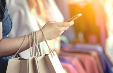 Lady carrying shopping bags in a store and on her mobile device